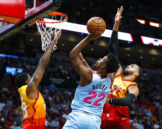 Miami Heat forward Jimmy Butler (22) goes to the basket between Utah Jazz forward Royce O'Neale (23) and center Rudy Gobert (27) during the first half of an NBA basketball game, Monday, Dec. 23, 2019, in Miami. (AP Photo/Joel Auerbach)