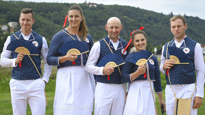 From left,  Czech track cyclist Tomas Babek, hammer thrower Katerina Safrankova, rider Miroslav Trunda, artistic gymnast Aneta Holasova and rider Miloslav Prihoda, pose wearing the new olympic uniforms for The Tokyo Olympic Summer Games 2020, in Prague, Czech Republic, Tuesday, June 22, 2021. The Olympics in Tokyo open July 23, when the world's athletes will march behind their flag-bearers. And when they do, the peanut gallery on what they're wearing will be open, too. The year-long wait due to the pandemic has given enthusiasts extra time to ponder what they love or hate. There's the Czech Republic and its traditional indigo block-print design with matching fans _ already the butt of some jokes. (Ondrej Deml, CTK via AP)