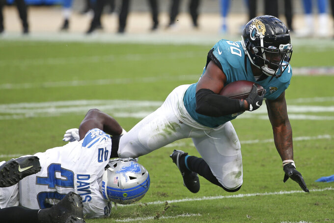 Jacksonville Jaguars running back James Robinson (30) dives for extra yardage as he is tackled by Detroit Lions linebacker Jarrad Davis, left, during the second half of an NFL football game, Sunday, Oct. 18, 2020, in Jacksonville, Fla. (AP Photo/Stephen B. Morton)