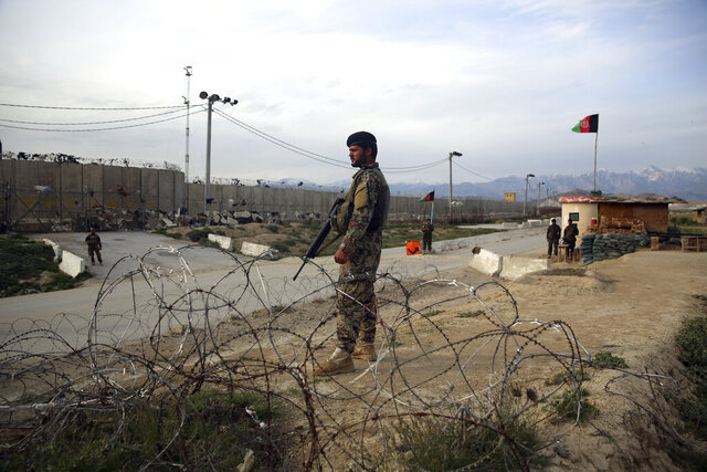 Afghan National Army soldiers stands guard at a checkpoint near the Bagram base in northern Kabul, Afghanistan, Wednesday, April 8, 2020. An Afghan official says the country has released 100 Taliban prisoners from Bagram, claiming they are part of 5,000 detainees who are to be freed under a deal between insurgents and U.S. But the Taliban says they have yet to verify those released were on the list they had handed over to Washington during negotiations. (AP Photo/Rahmat Gul)