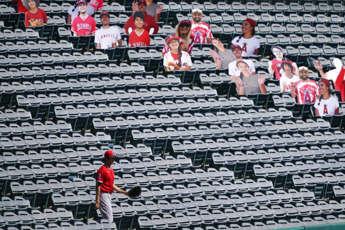 Los Angeles Angels designated hitter Shohei Ohtani (17) looks for stray baseballs in the stands near cutouts of fans during practice at Angels Stadium on Friday, July 3, 2020, in Anaheim, Calif. (AP Photo/Ashley Landis)