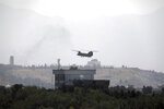 A U.S. Chinook helicopter flies over the U.S. Embassy in Kabul, Afghanistan, Sunday, Aug. 15, 2021. Helicopters are landing at the U.S. Embassy in Kabul as diplomatic vehicles leave the compound amid the Taliban advanced on the Afghan capital. (AP Photo/Rahmat Gul)