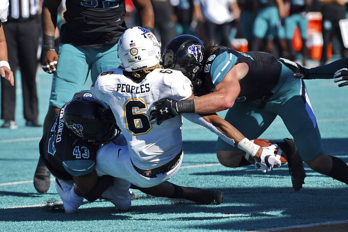 Coastal Carolina's Silas Kelly (29) and Enok Makonzo (43) tackle Appalachian State running back Camerun Peoples (6) during the first half of an NCAA college football game Saturday, Nov. 21, 2020, in Conway, S.C. (AP Photo/Richard Shiro)