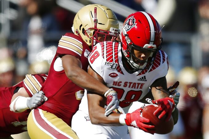 Boston College defensive back Jason Maitre, left, tackles North Carolina State wide receiver Devin Carter (88) during the first half of an NCAA college football game in Boston, Saturday, Oct. 19, 2019. (AP Photo/Michael Dwyer)