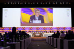 Thomas Bach, president of the International Olympic Committee (IOC), is seen on a video screen as he delivers a speech during the 135th Session of the IOC on the sideline of the the 3rd Winter Youth Olympic Games Lausanne 2020, at the SwissTech Convention Centre, in Lausanne, Switzerland, Friday, Jan. 10, 2020. (Laurent Gillieron/Keystone via AP)