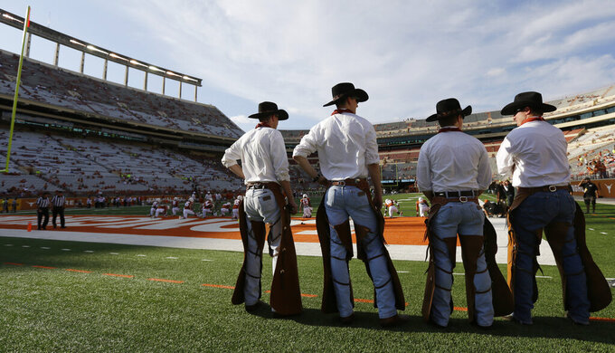 FILE - In this Aug. 30, 2014, file photo, members of The Texas Cowboys stand on the sidelines before an NCAA college football game between Texas and North Texas in Austin, Texas. On Wednesday, March 28, 2019, The University of Texas has suspended the spirit team for six years after an investigation found that a student death could have been avoided if a team retreat marked by hazing had been better managed. (AP Photo/Eric Gay, File)