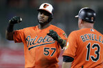 Baltimore Orioles' Hanser Alberto (57) gestures toward the dugout after his single off Toronto Blue Jays relief pitcher Justin Shafer scored Chris Davis during the seventh inning of a baseball game, Saturday, Aug. 3, 2019, in Baltimore. Orioles first base coach Arnie Beyeler (13) looks on. (AP Photo/Julio Cortez)