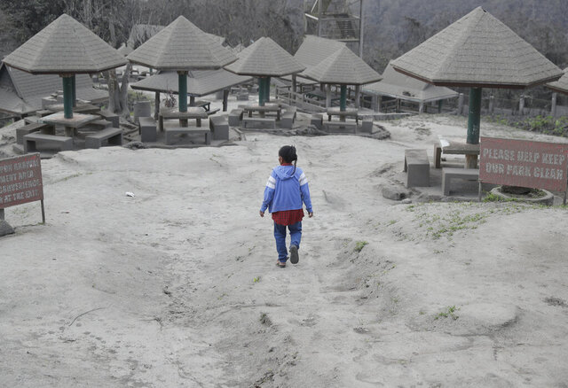 A woman walks along a park covered in volcanic-ash at a town near Taal volcano in Tagaytay, Cavite province, southern Philippines on Sunday Jan. 19, 2020. Philippine officials said Sunday the government will no longer allow villagers to return to a crater-studded island where an erupting Taal volcano lies, warning that living there would be
