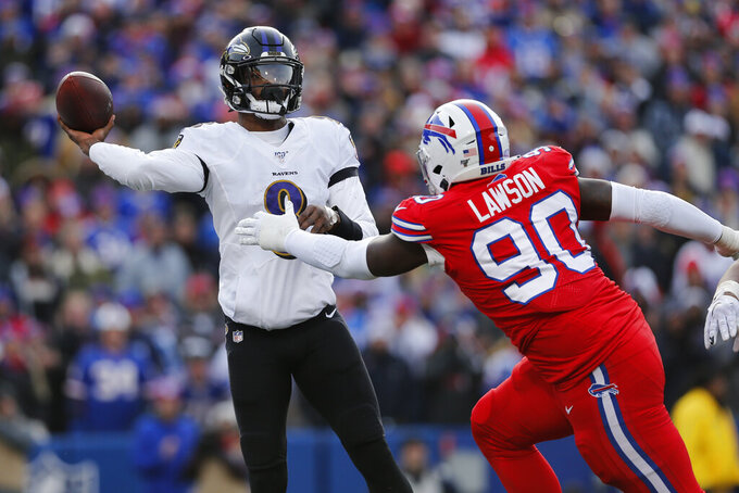Baltimore Ravens quarterback Lamar Jackson (8) gets off a pass under pressure by Buffalo Bills defensive end Shaq Lawson (90) during the first half of an NFL football game in Orchard Park, N.Y., Sunday, Dec. 8, 2019. (AP Photo/John Munson)