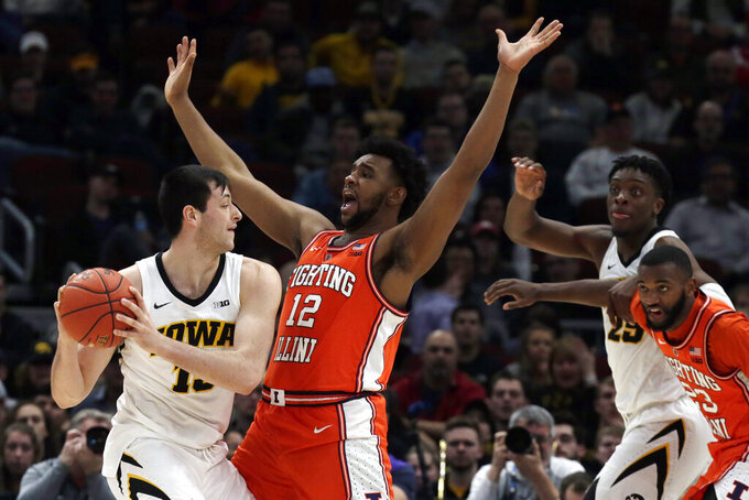 Iowa's Ryan Kriener (15) looks to pass against Illinois's Adonis De La Rosa (12) during the second half of an NCAA college basketball game in the second round of the Big Ten Conference tournament, Thursday, March 14, 2019, in Chicago. (AP Photo/Kiichiro Sato)