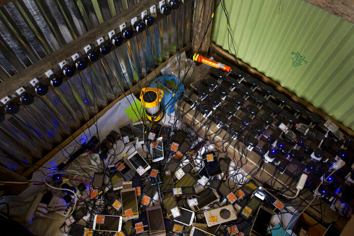 FILE- In this Saturday, Sept. 23, 2017 file photo, dozens of mobile phones charge in a makeshift shop for a price of five taka (US$ 0.06), at a Rohingya refugee camp in Lambashia, near Kutupalong. An official said Tuesday, Sept. 3, 2019, Bangladesh's telecommunications regulatory body has asked operators to shut down cellphone services in sprawling camps in the southeast where hundreds of thousands of Rohingya refugees from Myanmar live, citing a security threat. (AP Photo/Bernat Armangue, File)