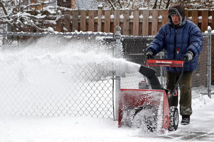 A man clears snow from his driveway of his house in Wheeling, Ill., Thursday, Feb. 13, 2020. (AP Photo/Nam Y. Huh)