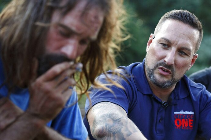 "In this Friday, Aug. 10, 2018 photo, Jamie Casey, right, speaks with Brian Peets at a homeless camp in New Bedford, Mass., on Friday, Aug. 10, 2018. ""For 20 years I fought and fought and fought against myself. Because you're your biggest enemy. You know that, right?"" Casey told Peets. (AP Photo/Michael Dwyer)"