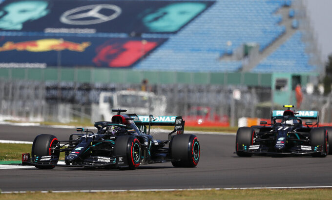 Mercedes driver Lewis Hamilton of Britain, left, and Mercedes driver Valtteri Bottas of Finland steer their cars during the third practice session at the 70th Anniversary Formula One Grand Prix at the Silverstone circuit, Silverstone, England, Saturday, Aug. 8, 2020. (AP Photo/Frank Augstein,Pool)