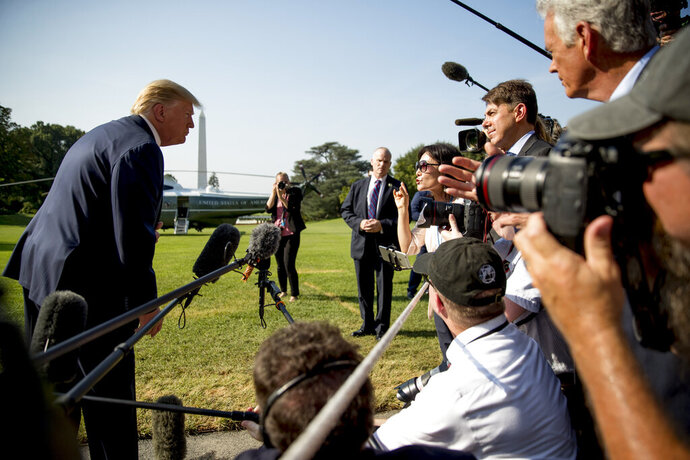 FILE - In this Wednesday, Aug. 7, 2019 file photo, President Donald Trump takes a question from a member of the media on the South Lawn of the White House in Washington before boarding Marine One. On Friday, Sept. 11, 2020, The Associated Press reported on a video circulating online incorrectly depicting Trump lost and meandering around the White House lawn. The original Aug. 7, 2019 video clip, available on C-SPAN, was edited to make it appear the president is experiencing dementia symptoms ahead of the election. (AP Photo/Andrew Harnik)