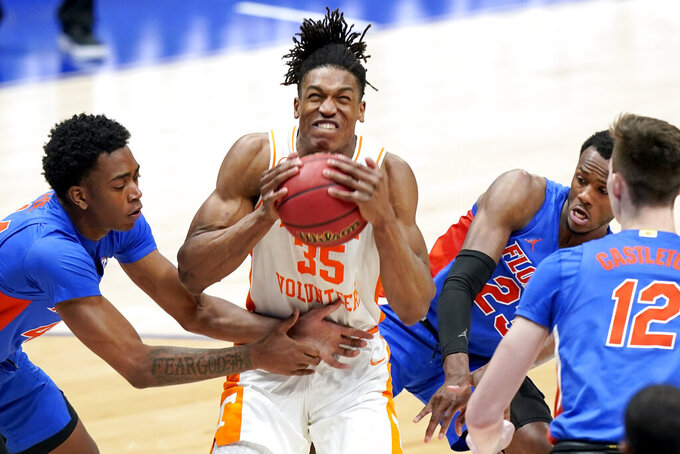 Tennessee's Yves Pons (35) pulls the ball away from Florida's Niels Lane, left, and Scottie Lewis (23) in the second half of an NCAA college basketball game in the Southeastern Conference Tournament Friday, March 12, 2021, in Nashville, Tenn. (AP Photo/Mark Humphrey)