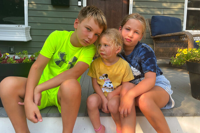 Forced to quarantine instead of attending the first days of school, Rylan, 10, Maddie, 3 and Amelia, 8, pose in Maplewood, N.J., Sept. 13, 2021, for an anti-back to school picture instead. Their mom, Associated Press editor Noreen Gillespie, decided to take the photo after her three kids were exposed to COVID and had to quarantine as their friends were going back to the classroom. (AP Photo/Noreen Gillespie)