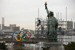 A worker installs scaffolding on the Statue of Liberty replica as a barge carrying the Olympic Rings floats in the water Friday, Jan. 17, 2020, in the Odaiba district of Tokyo. (AP Photo/Jae C. Hong)