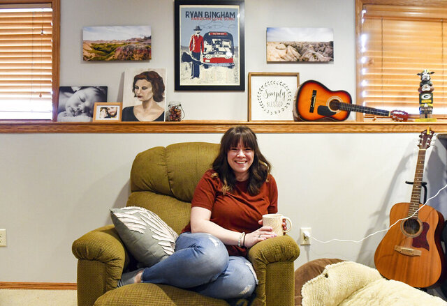 Carly Kewley, the woman behind CK Design, sits surrounded by art on Tuesday, Feb. 18, 2020, at her home in Sioux Falls, S.D. (Erin Bormett/The Argus Leader via AP)/