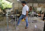 In this June 12, 2020 photo, Sri Lankan entrepreneur Nishantha Abeyrathne checks a paddle sink that is made at his workshop in Paththanduwana village in Sri Lanka. Abeyrathne's company seized upon an opportunity when factories in Sri Lanka were allowed to reopen; the government required owners to install sinks so employees could wash their hands, and Abeyrathne designed one with a foot paddle so workers wouldn't have to touch the faucet.  (AP Photo/Eranga Jayawardena)