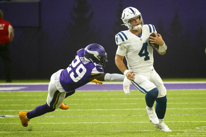 Indianapolis Colts quarterback Sam Ehlinger (4) runs from Minnesota Vikings defensive back Kris Boyd (29) during the first half of an NFL football game, Saturday, Aug. 21, 2021, in Minneapolis. (AP Photo/Jim Mone)
