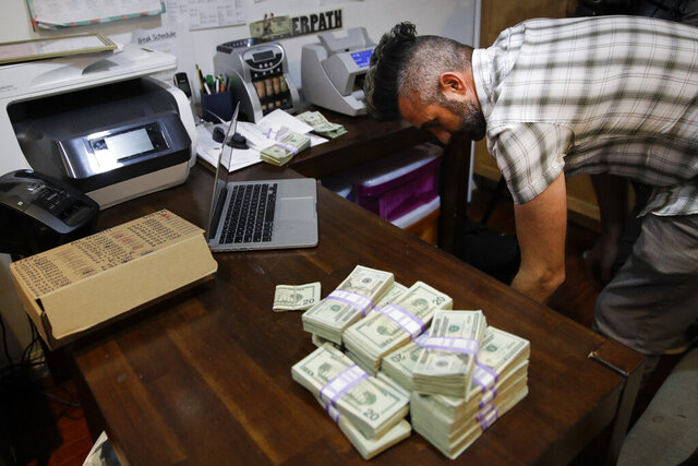 FILE - In this June 27, 2017, file photo, bundles of $20 bills are placed on a table as Jerred Kiloh, owner of the Higher Path medical marijuana dispensary, prepares a trip to Los Angeles City Hall to pay his monthly tax payment in cash in Los Angeles. The leading cannabis industry group in California announced Tuesday, Jan. 19, 2021, it had reached an agreement with a state credit union that will provide access to checking and other banking services for marijuana companies, ending what had been a longstanding obstacle for many businesses. (AP Photo/Jae C. Hong, File)