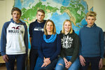 Silke Backsen, center poses with her children Hannes, left, Paul, second from left, Sophie second from right and Jakob, right, in front of a map of the world at the office of the environment organization Greenpeace in Berlin, Wednesday, Oct. 30, 2019. Silke Backsen and her family are one of the three families taking Chancellor Angela Merkel to court, arguing that her government isn't doing enough to tackle climate change. (AP Photo/Markus Schreiber)