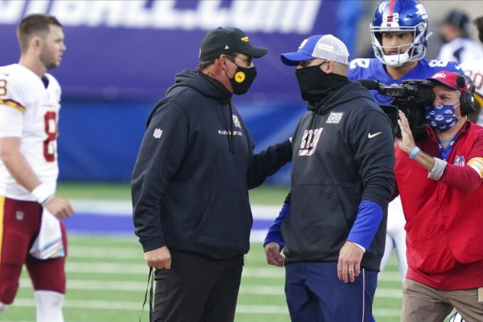 Washington Football Team's Ron Rivera, left, talks to New York Giants' Joe Judge, right, after an NFL football game Sunday, Oct. 18, 2020, in East Rutherford, N.J. The Giants won 20-19. (AP Photo/John Minchillo)