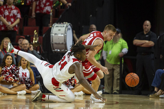 Wisconsin guard Brad Davison (34) and Nebraska forward Yvan Ouedraogo (24) scramble for a loose ball during the first half of an NCAA college basketball game in Lincoln, Neb., Saturday, Feb. 15, 2020. (AP Photo/John Peterson)