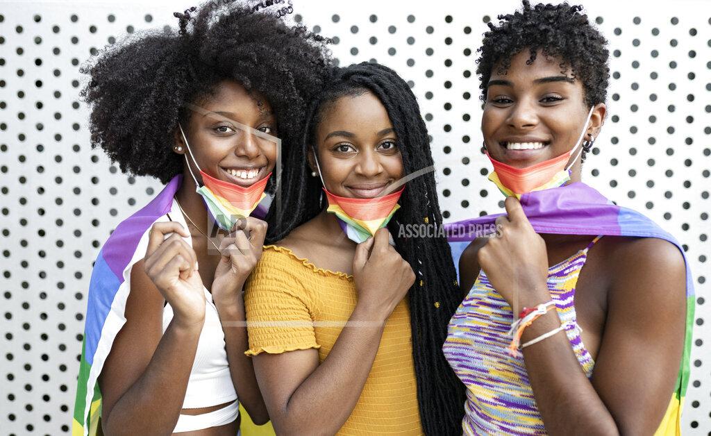 Smiling lesbian women wearing rainbow flag protective face masks