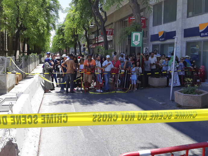 People are prevented to enter a security area after an explosion in Tunis, Thursday June 27, 2019. The Tunisian Interior ministry said one police officer has died in the suicide bombing targeting a police patrol in a busy commercial street in central Tunis. (AP Photo/Riadh Dridi)