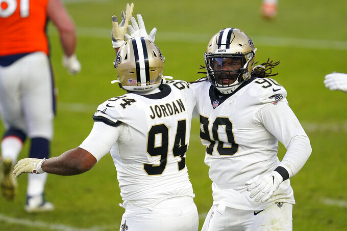 New Orleans Saints defensive end Cameron Jordan (94) celebrates his sack against the Denver Broncos with defensive tackle Malcom Brown (90) during the second half of an NFL football game, Sunday, Nov. 29, 2020, in Denver. (AP Photo/David Zalubowski)