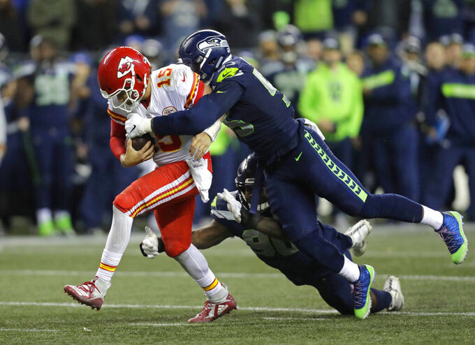 FILE - In this Dec. 23, 2018, file photo, Kansas City Chiefs quarterback Patrick Mahomes (15) is tackled by Seattle Seahawks defensive end Frank Clark, right, during the second half of an NFL football game, in Seattle. The Kansas City Chiefs have agreed to acquire defensive end Frank Clark from the Seattle Seahawks in exchange for a first-round draft pick this year and a second-round pick in 2020. Almost immediately after word leaked of the trade on Tuesday, April 23, 2019, Clark and the Chiefs worked quickly to reach agreement on a five-year contract worth up to $105 million, according to a person with knowledge of the deal. The person spoke to The Associated Press on the condition of anonymity because the deal had not been announced by either team and was still pending a physical. (AP Photo/Stephen Brashear, File)