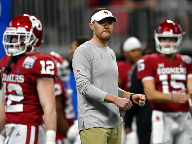 """FILE - In this Dec. 28, 2019, file photo, Oklahoma head coach Lincoln Riley, center, stands with his team before the Peach Bowl NCAA semifinal college football playoff game against LSU in Atlanta. College football teams set to play this fall are trying to help their depth amid the coronavirus pandemic by finding players capable of playing multiple positions. Riley says it is """"something every coach in the country is thinking about right now."""" That's because positive tests, contact tracing and quarantines could abruptly alter any roster. (AP Photo/John Amis, File)"""