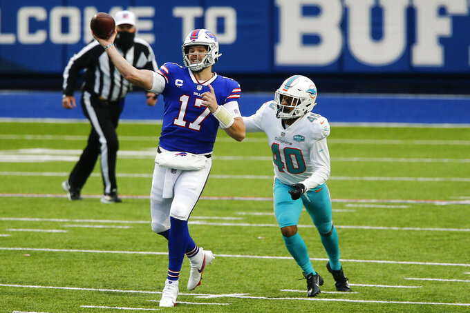 Buffalo Bills quarterback Josh Allen (17) throws a touchdown pass to wide receiver John Brown A Miami Dolphins defensive back Nik Needham (40) pressures during the first half of an NFL football game, Sunday, Jan. 3, 2021, in Orchard Park, N.Y. (AP Photo/John Munson)