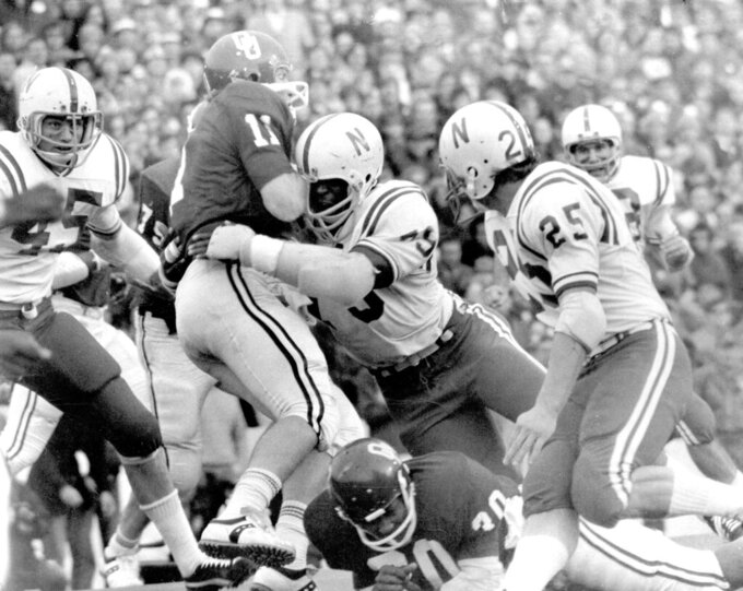 FILE - In this Nov. 25, 1971, file photo, Nebraska's Rich Glover (79) brings down Oklahoma quarterback Jack Mildren (11) as Nebraska defenders Bob Terrio (45) and Dave Mason (25) close in during a college football game in Norman, Okla., on Thanksgiving Day. The game on Thanksgiving 50 years ago is back in the spotlight as Nebraska and Oklahoma renew their rivalry on Saturday, Sept. 18, 2021. (Lincoln Journal Star via AP, File)