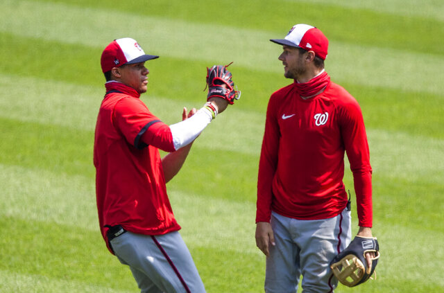 Washington Nationals shortstop Trea Turner, right, watches teammate Juan Soto, catches a fly ball during a baseball intrasquad game at Nationals Park, Sunday, Aug. 2, 2020, in Washington. (AP Photo/Manuel Balce Ceneta)