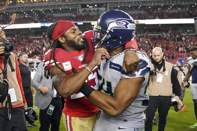 San Francisco 49ers cornerback Richard Sherman, left, hugs Seattle Seahawks middle linebacker Bobby Wagner after an NFL football game in Santa Clara, Calif., Monday, Nov. 11, 2019. The Seahawks won 27-24 in overtime. (AP Photo/Tony Avelar)
