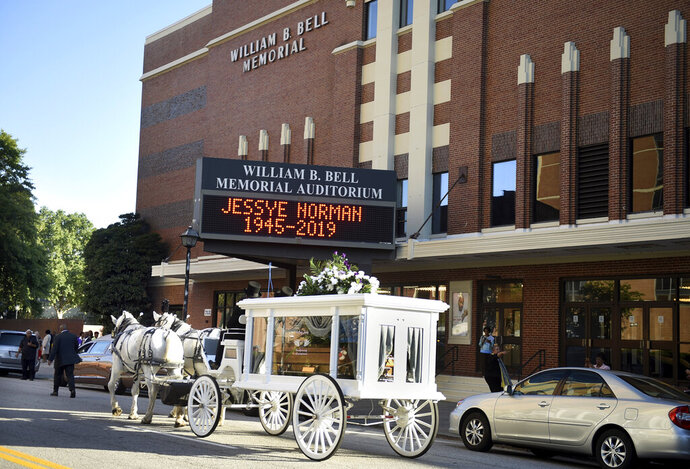 A horse-drawn hearse containing the body of opera star Jessye Norman passes by the Bell Auditorium, site of her funeral, in Augusta, Ga., Saturday, Oct. 12, 2019. Norman died Sept. 30 at age 74. She was awarded the National Medal of Arts, the Kennedy Center Honor and four Grammy Awards. (Michael Holahan/The Augusta Chronicle via AP)