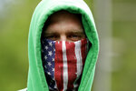 FILE - In this May 4, 2020, file photo, a man wears a mask as he waits in line outside the Warrensburg License Office in Warrensburg, Mo. (AP Photo/Charlie Riedel, File)