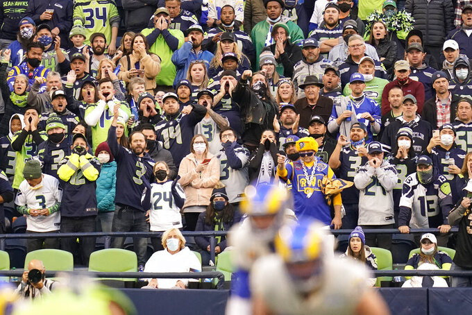 Despite a mask mandate at Lumen Field most fans go without as they cheer during the first half of an NFL football game between the Seattle Seahawks and the Los Angeles Rams, Thursday, Oct. 7, 2021, in Seattle. (AP Photo/Elaine Thompson)