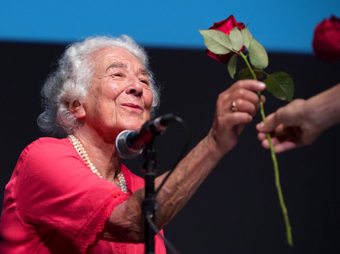 FILE - In this Sept. 15, 2016 file photo British writer Judith Kerr holds a rose in Berlin, Germany. Judith Kerr, author and illustrator of the bestselling