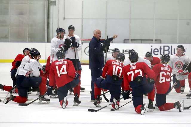 File-Florida Panthers head coach Joel Quenneville, center, talks with his players during NHL hockey training camp, Tuesday, July 14, 2020, in Coral Springs, Fla. The Panthers just announced they'll be doing some meetings, etc. outside during training camp to promote distancing, etc., during the pandemic. (AP Photo/Lynne Sladky, File)