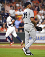 New York Yankees starting pitcher Jonathan Loaisiga, right, walks off the mound as Houston Astros' Jose Altuve, back left, rounds the bases after hitting a solo home run during the third inning of a baseball game, Tuesday, April 9, 2019, in Houston. The home run was Altuve's 100th for his career. (AP Photo/Eric Christian Smith)