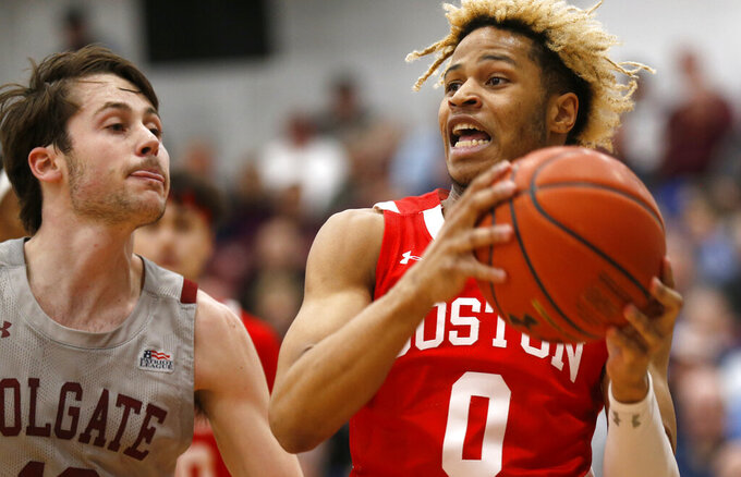 Boston University's Ethan Brittain-Watts, right, drives to the basket past Colgate's Jack Ferguson, left, in the first half of the NCAA Patriot League Conference basketball championship at Cotterell Court, Wednesday, March 11, 2020, in Hamilton, N.Y. (AP Photo/John Munson)
