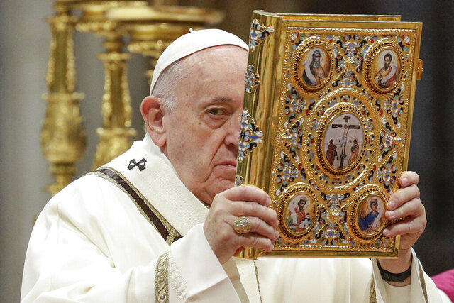 Pope Francis holds up the book of Gospels as he celebrates an Epiphany Mass in St. Peter's Basilica at the Vatican, Monday, Jan. 6, 2020. (AP Photo/Andrew Medichini)
