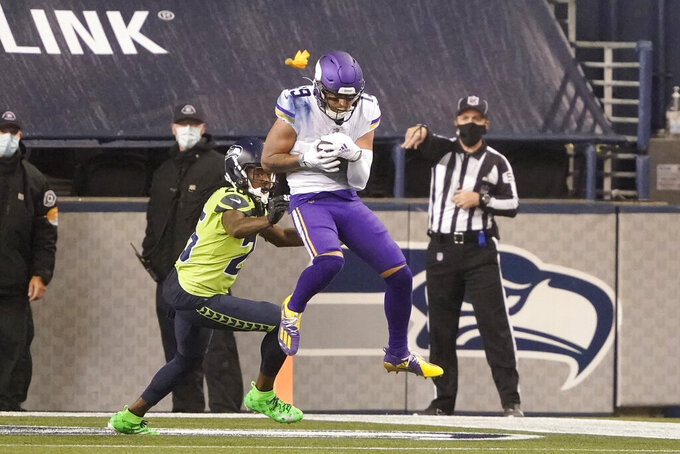 Minnesota Vikings' Adam Thielen, right, catches a touchdown pass as Seattle Seahawks' Shaquill Griffin defends during the second half of an NFL football game, Sunday, Oct. 11, 2020, in Seattle. (AP Photo/Ted S. Warren)