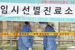 Health officials wearing protective gear wait for people at a makeshift clinic for COVID-19 testing in Seoul, South Korea, Monday, Aug. 10, 2020. The signs reads;