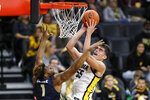Iowa center Luka Garza (55) drives to the basket over Oral Roberts forward Elijah Lufile during the second half of an NCAA college basketball game, Friday, Nov. 15, 2019, in Iowa City, Iowa. (AP Photo/Charlie Neibergall)