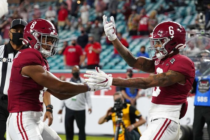 Alabama wide receiver John Metchie III, left, congratulates wide receiver DeVonta Smith, after Smith scored a touchdown against Ohio State during the first half of an NCAA College Football Playoff national championship game, Monday, Jan. 11, 2021, in Miami Gardens, Fla. (AP Photo/Chris O'Meara)